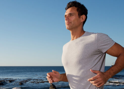 Man running by the ocean after FlexSure treatments